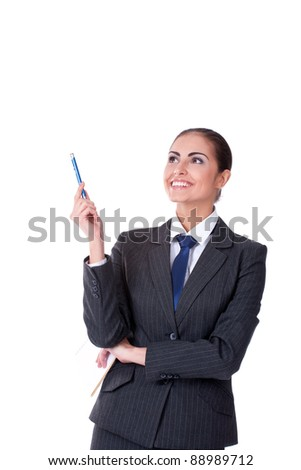 Young businesswoman standing with pen pointing on copyspace