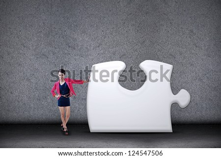 Young businesswoman stands beside the missing puzzle - stock photo