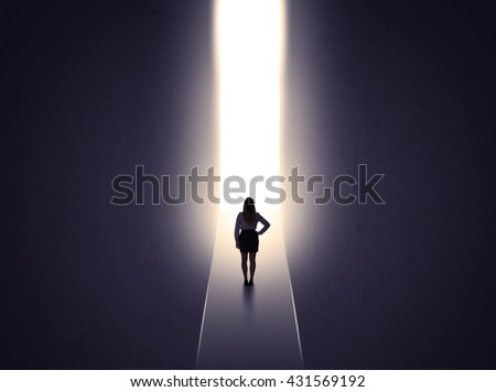 Young businesswoman stands in dark tunnel and looks in the glowing end - stock photo