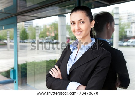 young businesswoman stands with her arms crossed outside an office building. she is smiling and looking at the camera,  horizontal shot - stock photo