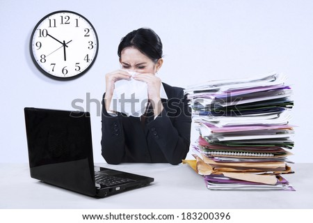 Young businesswoman stressed with laptop and many paper at work