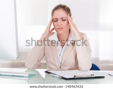 Young Businesswoman Suffering From Headache At Office - stock photo