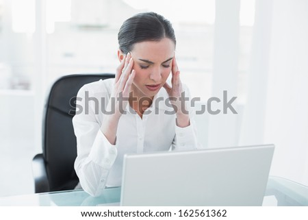 Young businesswoman suffering from headache in front of laptop at office desk - stock photo