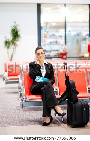 young businesswoman talking on cell phone at airport - stock photo