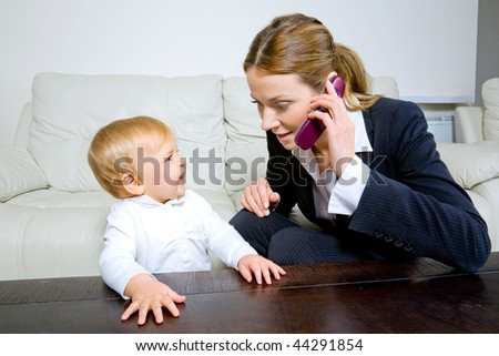 young businesswoman  talking on cell phone with her baby daughter - stock photo