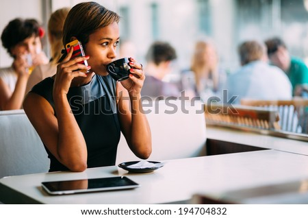 Young businesswoman talking on the phone in coffee shop - stock photo