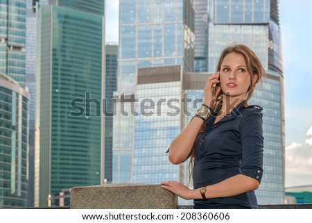 Young businesswoman talking on the phone near skyscrapers