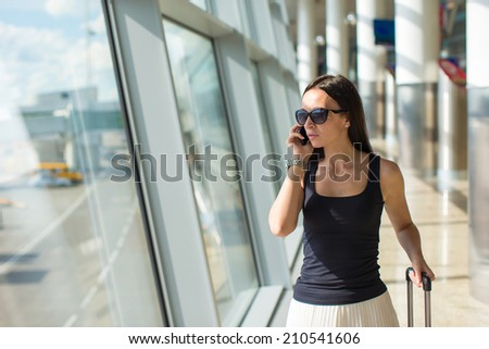 Young businesswoman talking on the phone while waiting for her flight - stock photo