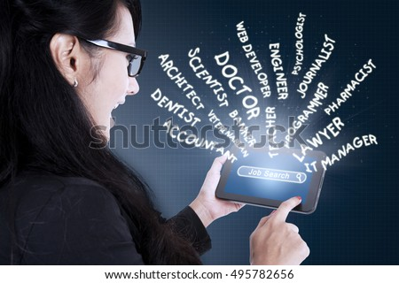 Young businesswoman touching a digital tablet screen and searching jobs. Concept of Job Search