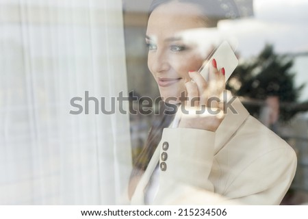 Young businesswoman using cell phone in office - stock photo