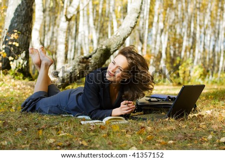 Young businesswoman using laptop on nature.