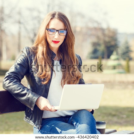 Young businesswoman using laptop sitting on bench in the park. European smiling student girl with notebook reading or learning in the park - stock photo