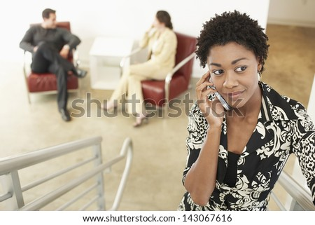 Young businesswoman using mobile phone on stairway with colleagues in background - stock photo