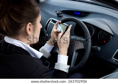 Young businesswoman using smartphone while driving car - stock photo