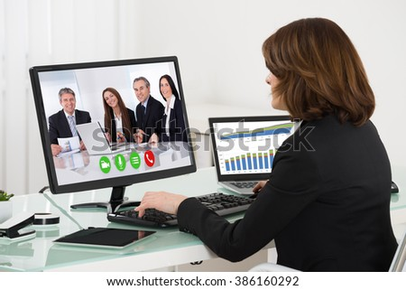 Young Businesswoman Videoconferencing With Colleagues On Computer At Desk
