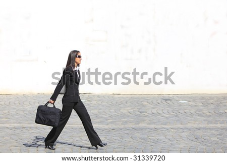 Young businesswoman walking along a cobbled street in front of a white wall.