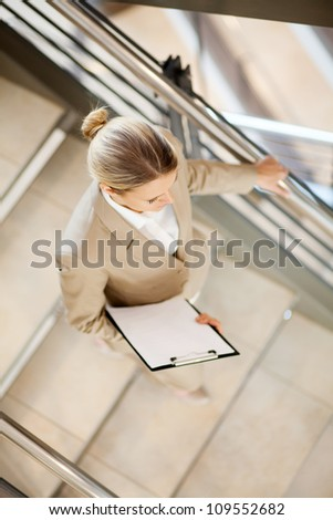 young businesswoman walking down stairs - stock photo