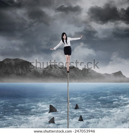 Young businesswoman walking on a rope bridge over a sea with shark on the below - stock photo