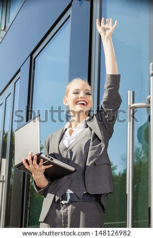 Young businesswoman waving her arm - stock photo