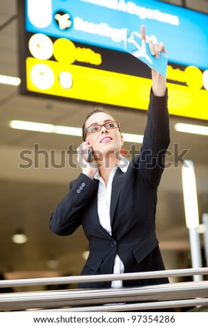 young businesswoman waving to someone while talking on cell phone at airport