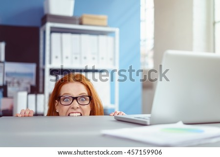 Young businesswoman wearing glasses crouching down biting her desk in wide eyed frustration