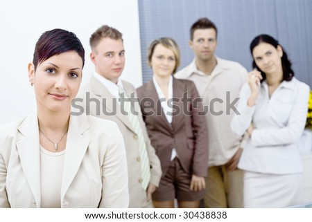 Young businesswoman wearing glasses posing in front, looking at camera, smiling. Four businesspersons standing in the background. - stock photo
