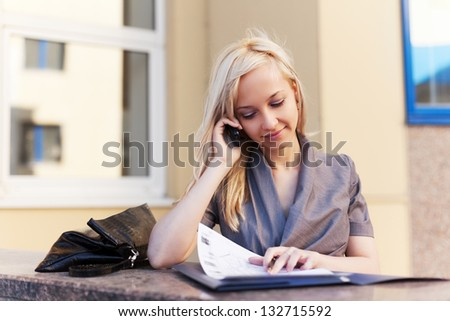 Young businesswoman with a folder calling on the phone - stock photo