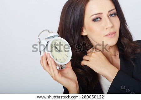 Young businesswoman with an alarm clock. In white studio