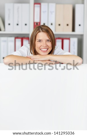 Young businesswoman with arms on white board at office - copyspace for text - stock photo