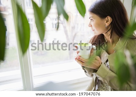 Young businesswoman with coffee cup looking through window at office - stock photo