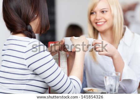 Young businesswoman with coworker holding coffee cup in office cafe - stock photo