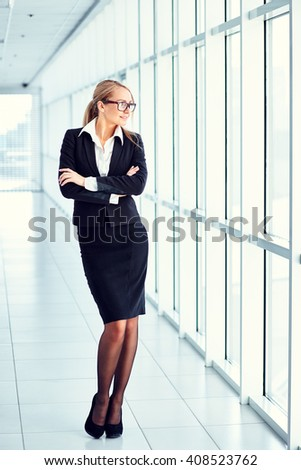 Young businesswoman with crossed arms standing in the business center. - stock photo