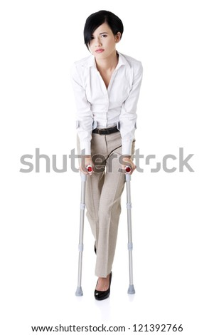 Young businesswoman with crutches, isolated on white. Disabled person in work. - stock photo