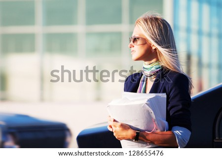 Young businesswoman with financial papers on the city street - stock photo