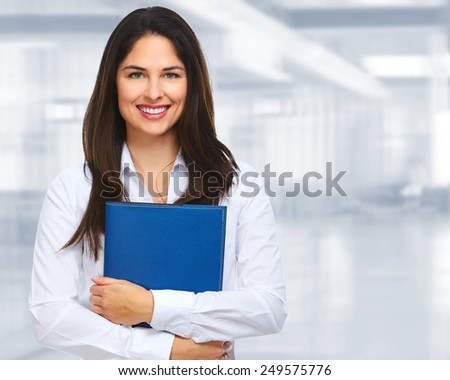 Young businesswoman with folder over office background. - stock photo