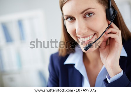 Young businesswoman with headset looking at camera with smile - stock photo