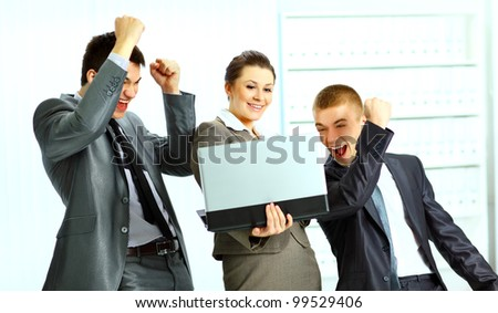 Young businesswoman with her colleagues using laptop and celebrating success of their company - stock photo