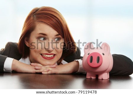Young businesswoman with her piggy bank.