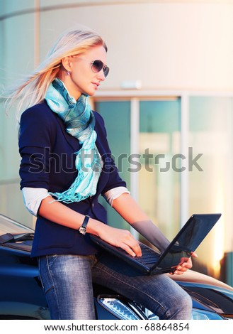 Young businesswoman with laptop on the parking. - stock photo