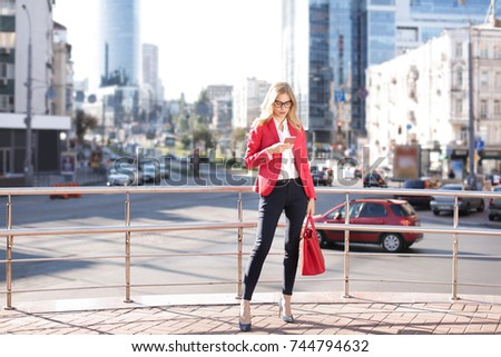 Young businesswoman with mobile phone outdoors