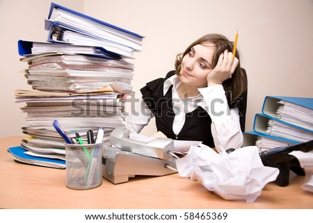 Young businesswoman with tons of documents thinking