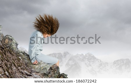 Young businesswoman with waving hair sitting on top of mountain - stock photo