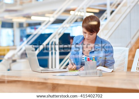 Young businesswoman working at modern desk behind glass - stock photo