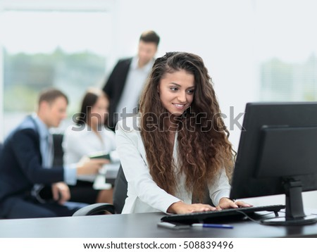 Young  businesswoman working in an office using computer with co