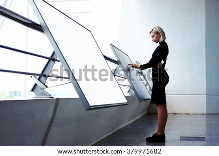 Young businesswoman working on interactive display while standing near another big computer monitor with blank copy space screen for your text message or content, elegant female selecting information - stock photo