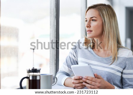 Young businesswoman working on tablet computer while drinking coffee in the office - stock photo