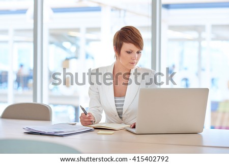 Young businesswoman working with a laptop at her desk - stock photo