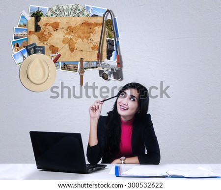 Young businesswoman working with laptop while dreaming a vacation to the famous place around the world - stock photo