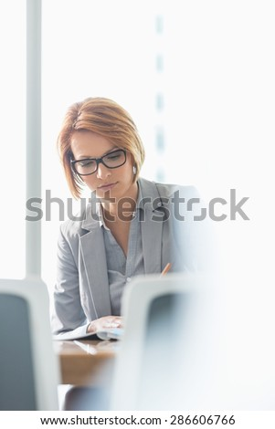 Young businesswoman writing at desk in office - stock photo