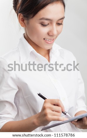 Young businesswoman writing something isolated on grey background